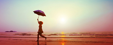 Woman running on the beach at sunset, holding an umbrella