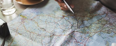 Hand holding a pen on a map