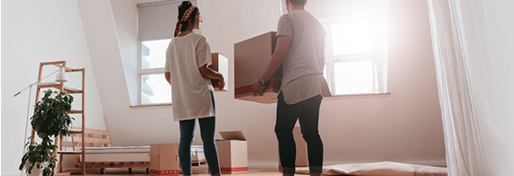 Young couple carrying boxes in an empty house