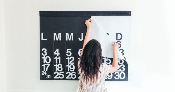 Young woman removes a page from a large calendar hanging on a wall
