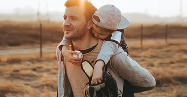 Man carrying his child on his back