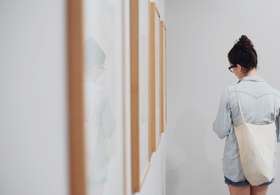Woman looking at paintings in gallery